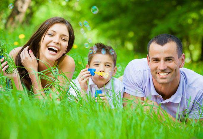 Photo of a family blowing bubbles while lying on grass