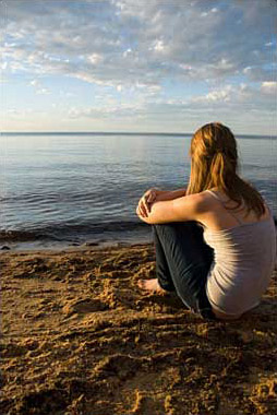 Photo of a teenage girl sitting on a beach looking toward the horizon